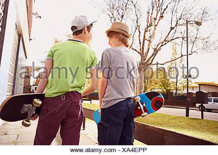 Boys carrying skateboards - Stock Photo