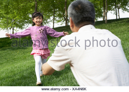 Young Girl Running Towards Man In Park With Arms Outstretched - Stock Photo
