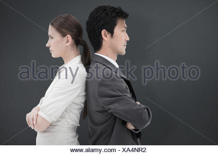 Composite image of portrait of serious business people standing back-to-back - Stock Photo