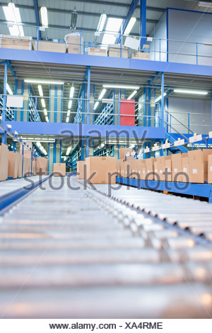 Boxes on conveyor belts in distribution warehouse - Stock Photo
