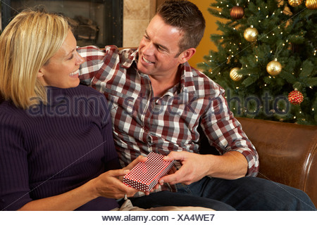 Couple Opening Presents In Front Of Christmas Tree - Stock Photo