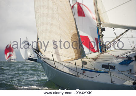 colorful spinnakers in front of the bow of a sailboat - Stock Photo
