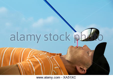 Man balancing golf ball on tee in his mouth - Stock Photo