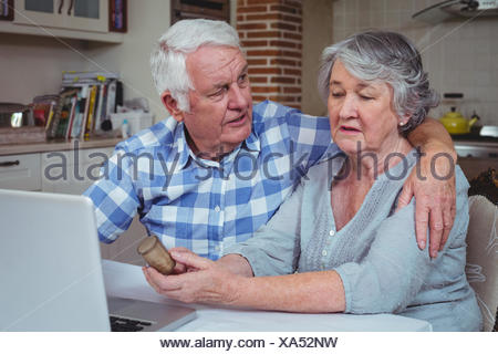 Senior man consoling wife holding pills container - Stock Photo