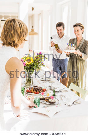 Senior woman carrying birthday cake to dining room table for party - Stock Photo
