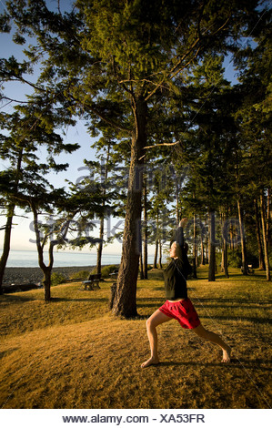 A womanduring a yoga pose at Kitty Coleman Beach campground.  Courtenay Comox Valley Vancouver Island British Columbia Canada. - Stock Photo