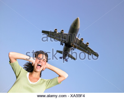 Woman covering ears and screaming with plane flying overhead. - Stock Photo