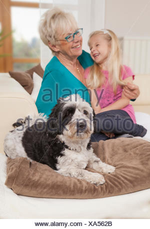 Senior woman with dog and granddaughter laughing in a living room, Bavaria, Germany - Stock Photo