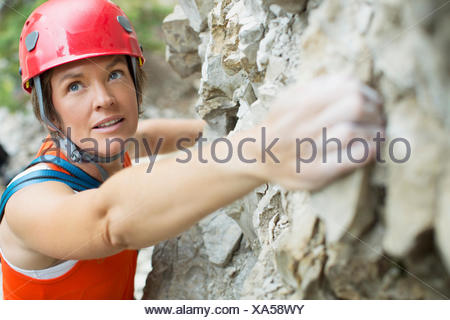 middle-aged female rock climber on rock face - Stock Photo