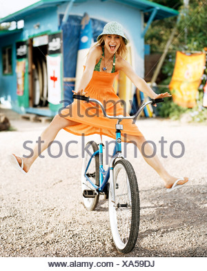 Female blonde hair wearing green swimsuit and orange strapless dress blue hat free wheeling on pushbike looking at camera mouth - Stock Photo