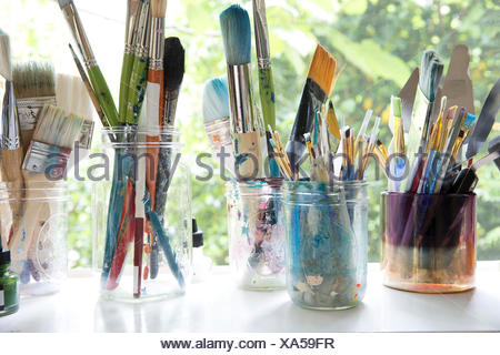 Row of jars with variety of artist paintbrushes on window sill  of artists studio - Stock Photo