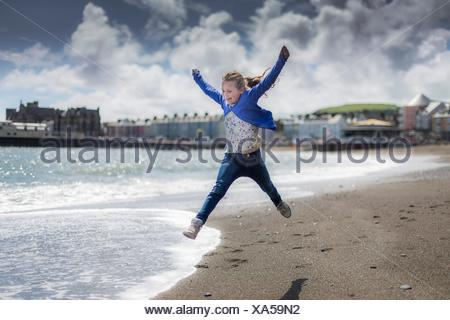 MODEL RELEASED. Girl leaping on the beach. - Stock Photo