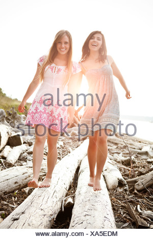 USA, Washington, Seattle, Two young women balancing on logs - Stock Photo