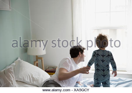 Father and son in pajamas looking out window - Stock Photo