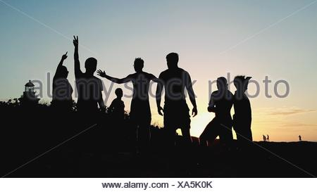 Silhouette Friends Enjoying On Field Against Clear Sky During Sunset - Stock Photo