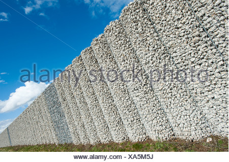 Gabion wall, mesh baskets filled with stones, noise protection wall on the Autobahn A9 motorway, Bavaria, Germany - Stock Photo