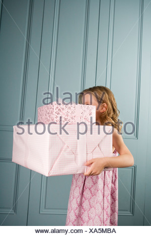 little girl carrying pile presents face obscured - Stock Photo