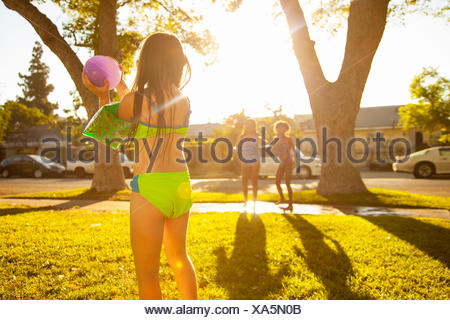 Girl chasing friends with water balloon in garden - Stock Photo