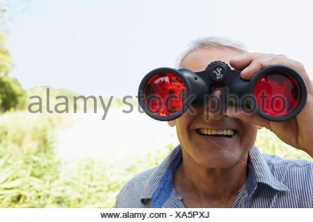 Senior man looking through field glass - Stock Photo