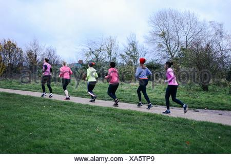 Six adult female runners running on park path - Stock Photo