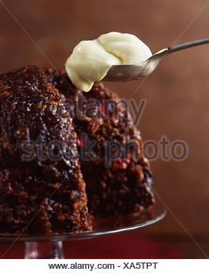 Christmas pudding with spoonful of brandy cream - Stock Photo