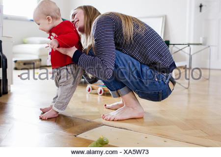 Mid adult woman holding baby daughter to take first steps - Stock Photo
