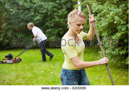 Woman with stick and man using manual lawn mower to cut grass - Stock Photo