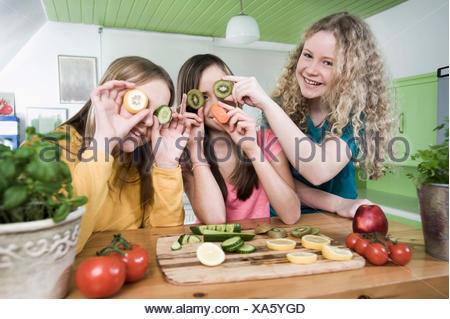 Girls in kitchen making faces with fruit - Stock Photo