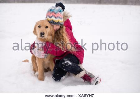 Young girl cuddling her Golden Retriever in snow - Stock Photo