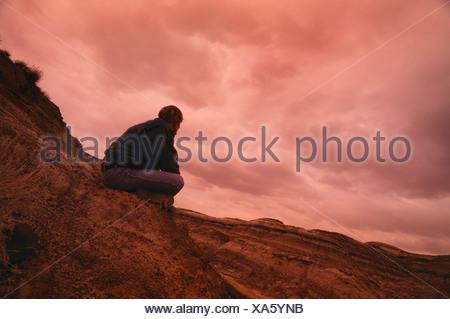 Man sitting on hill - Stock Photo