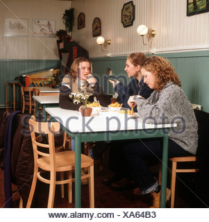 Teenagers eating pommes frites in luncheonette. - Stock Photo
