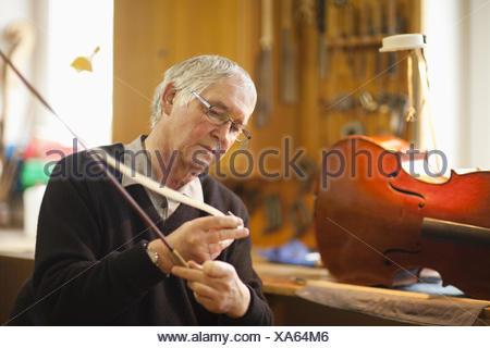Senior violin maker putting hair on violin bow - Stock Photo