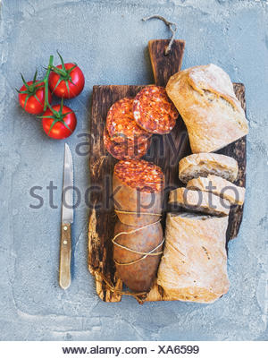 Wine snack set. Hungarian mangalica pork salami sausage, rustic bread and fresh tomatoes on dark wooden board over a rough grey- - Stock Photo