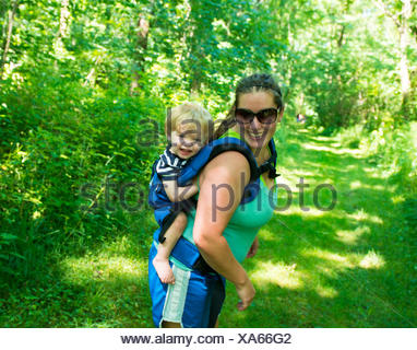 Woman walking through forest carrying son on her back - Stock Photo