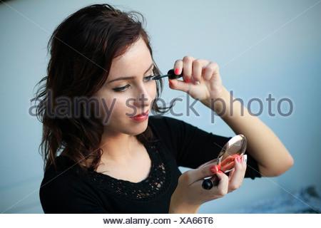 Woman putting on mascara, looking into hand mirror, Copenhagen, Denmark - Stock Photo