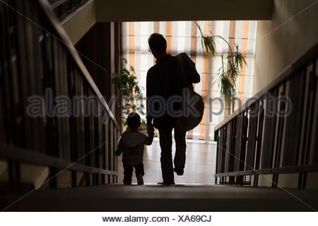 Father and son walking down stairs holding hands - Stock Photo