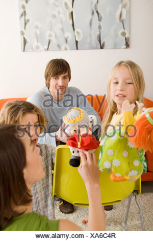 Family playing with glove puppets - Stock Photo