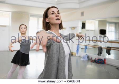 Female instructor guiding ballet dancer practicing in dance studio - Stock Photo