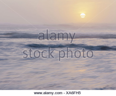 Olympic National park View out over the sea and gentle swell in the waters off the shore Sunset Sun sinking below the horizon - Stock Photo