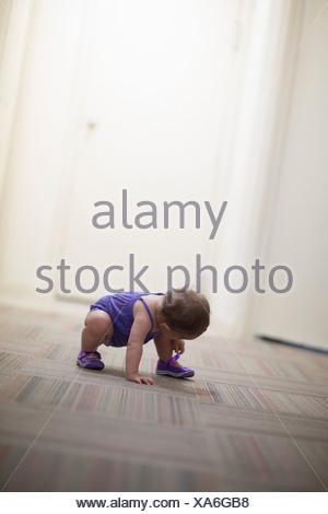 Toddler girl crouching on floor - Stock Photo