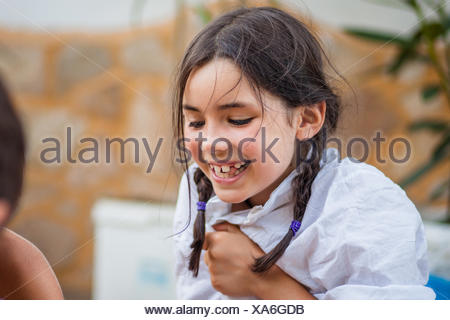 Little girl (6-7) with braids and white shirt laughing happily - Stock Photo