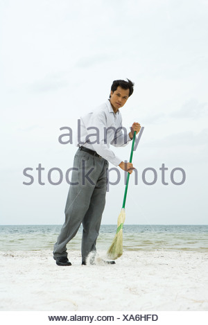 Man standing on beach sweeping with broom, looking at camera - Stock Photo