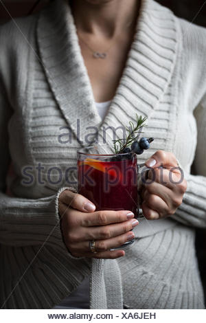A woman is photographed with a glass of blueberry hot toddy in her hand - Stock Photo