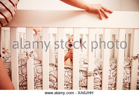 Baby hugging soft toy in crib