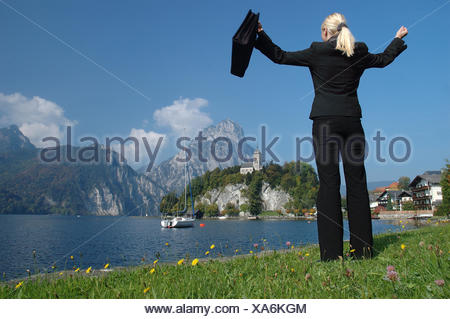 Blonde woman wearing a suit standing at the Traunsee Lake, celebrating her success, Traunkirchen, Upper Austria, Europe - Stock Photo