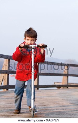 Boy riding scooter on dock over lake - Stock Photo