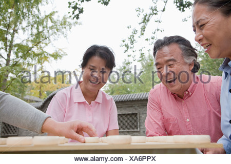 Group of mature people playing Chinese checkers - Stock Photo