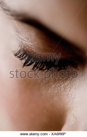 Detail of woman's face showing left eye, looking down - Stock Photo