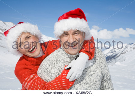Portrait of happy senior couple wearing Santa hats in mountains on winter day - Stock Photo