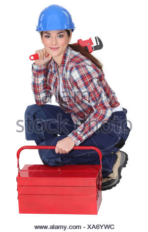 Portrait of a tradeswoman with a pipe wrench and a toolbox - Stock Photo